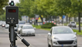 a mobile handheld speed gun on a tripod faceing oncoming traffic